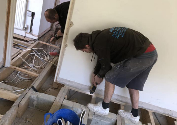 Two men wiring electrics into the floor.