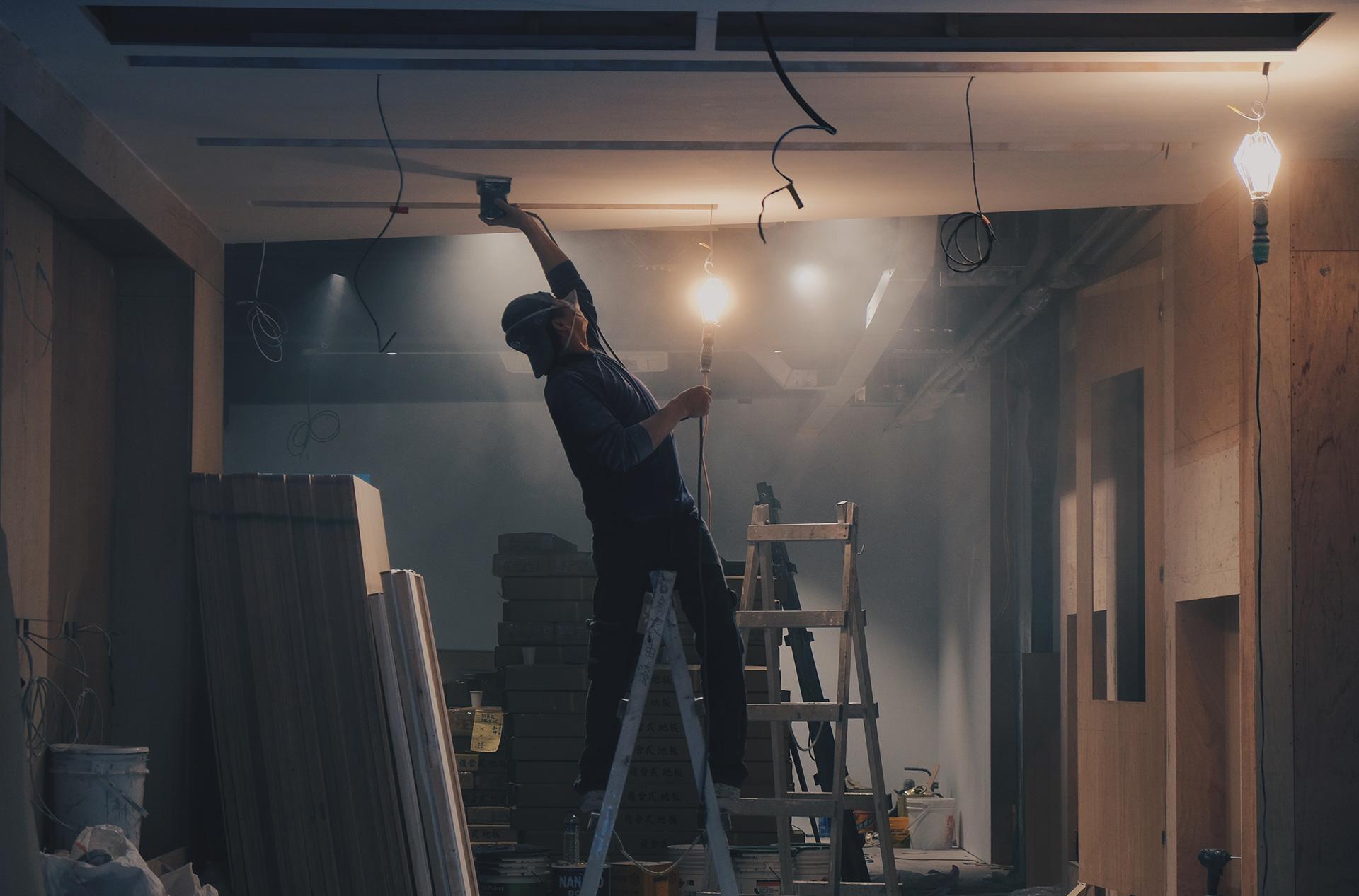 Wordman sanding down ceiling.
