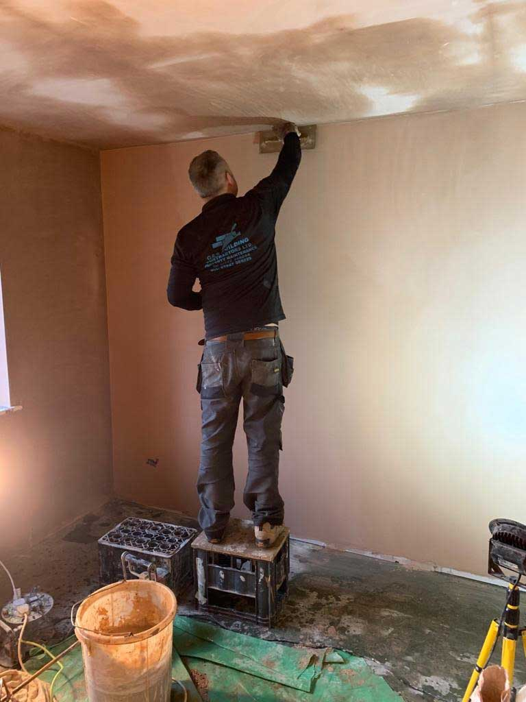 Man working on plastering a wall and ceiling.