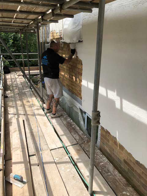 Man rendering an outside wall of a house.