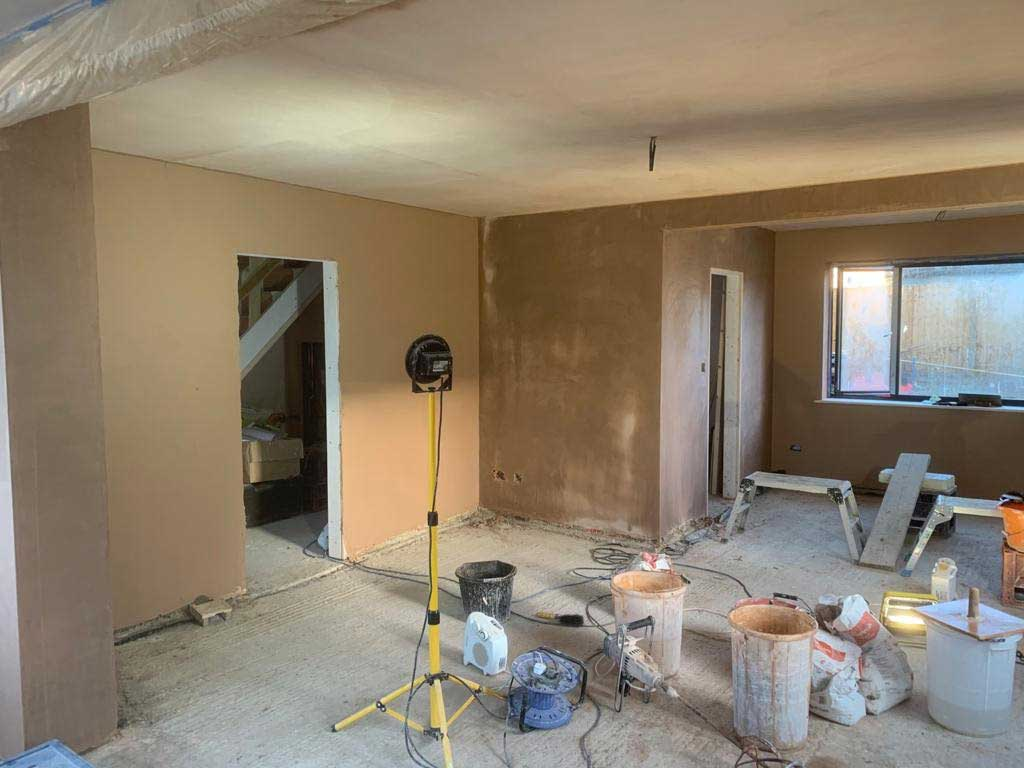 Inside of house being plastered with work equipment.